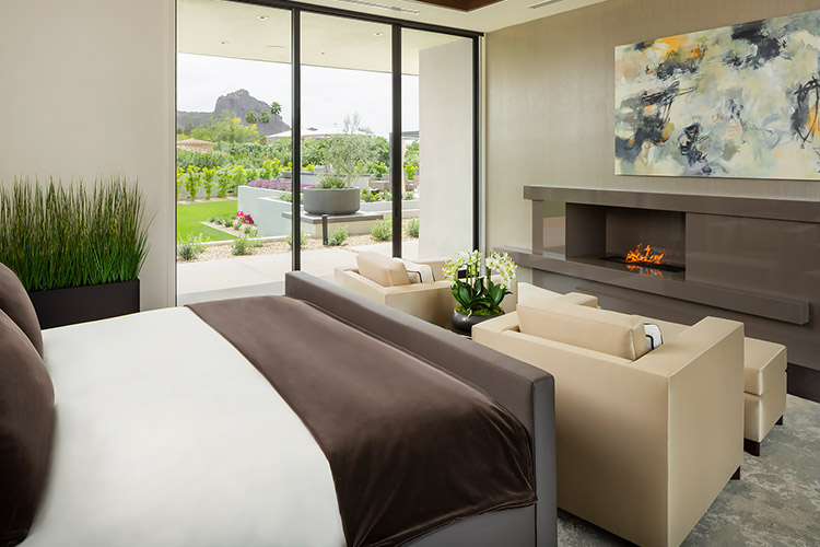 Bedroom in contemporary custom home with fireplace