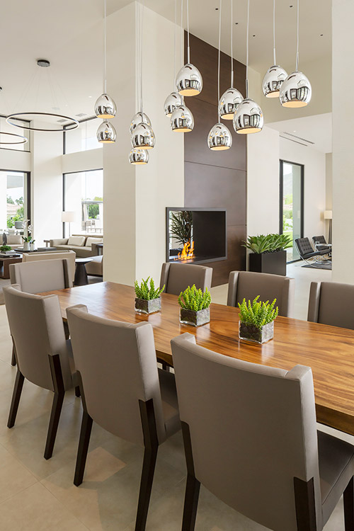 Dining room in contemporary custom home with hanging light fixtures
