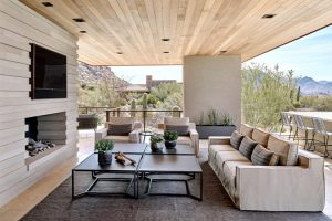 Outdoor living room with TV and fireplace in custom home