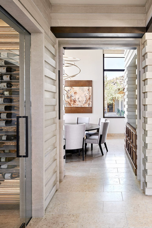 Wine cellar and dining room in desert prairie custom home