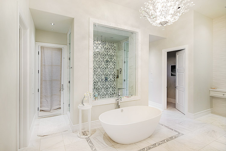 Bathroom in custom home with white walls and floors and standalone tub