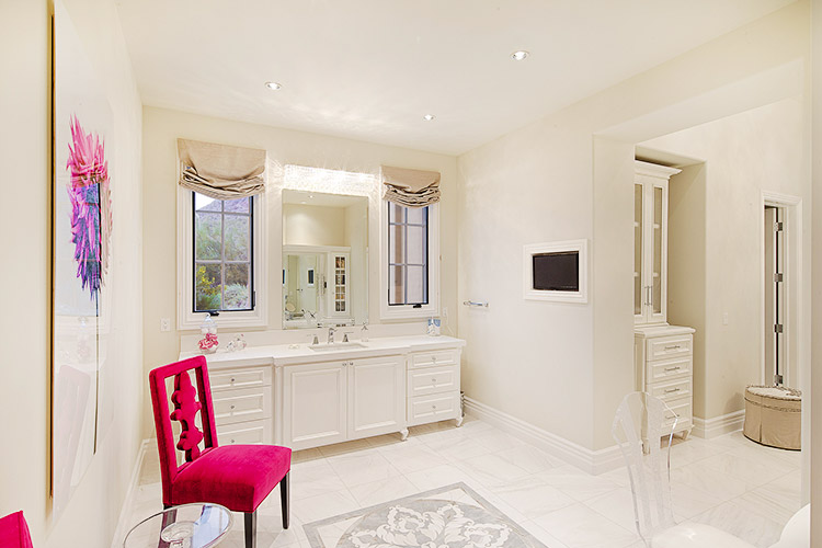 Bathroom in custom home with white walls and floors and pink chairs