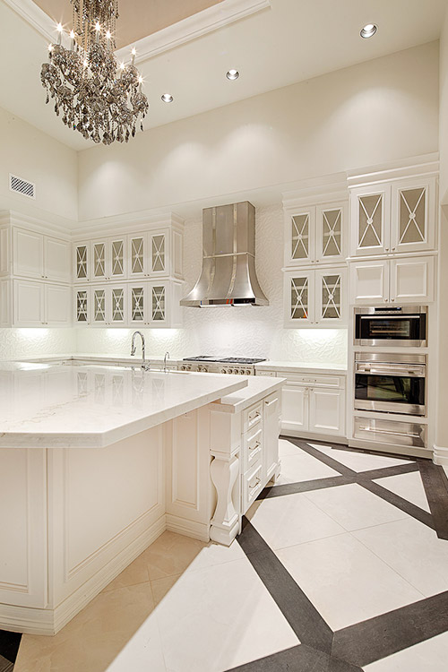 Kitchen in custom home with chandelier and white cabinets and counters