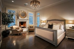 Custom home bedroom with fireplace and chandelier