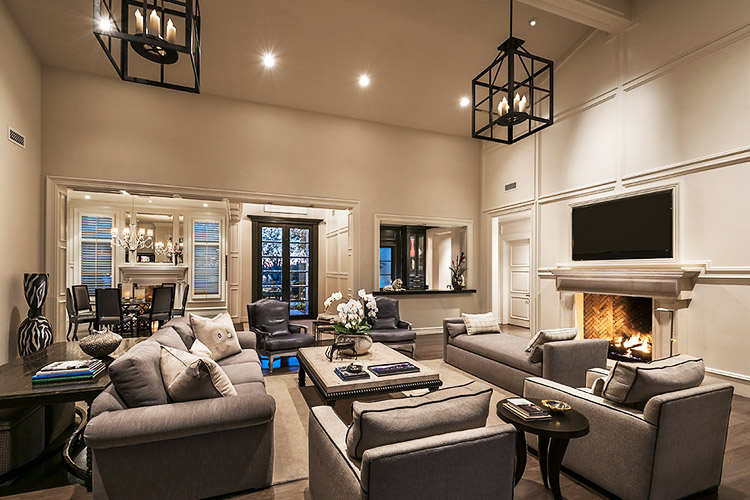 Living rom in custom home with couches, chairs, and a fireplace