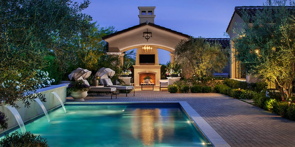 Exterior of custom home with pool and water feature