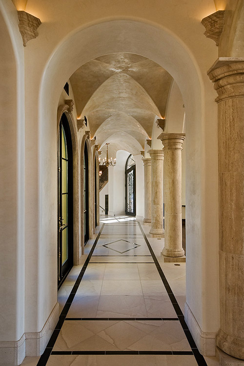 Hallway with pillars and sconces in custom home