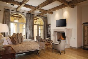 Custom bedroom with fireplace and wooden beams