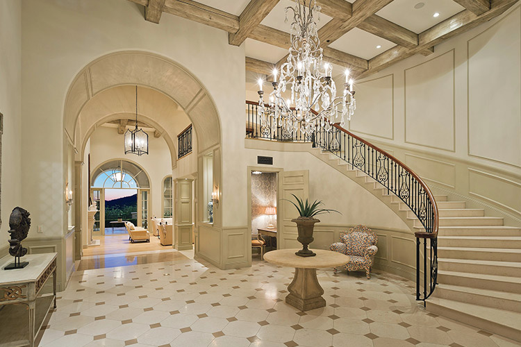 Luxury custom home with large staircase, chandelier and hallway leading to patio