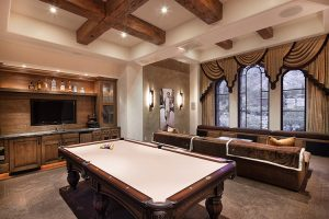 Custom entertainment room with bar, pool table, and couch