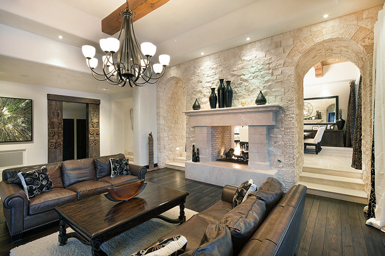Living room in custom home with fireplace and stonework