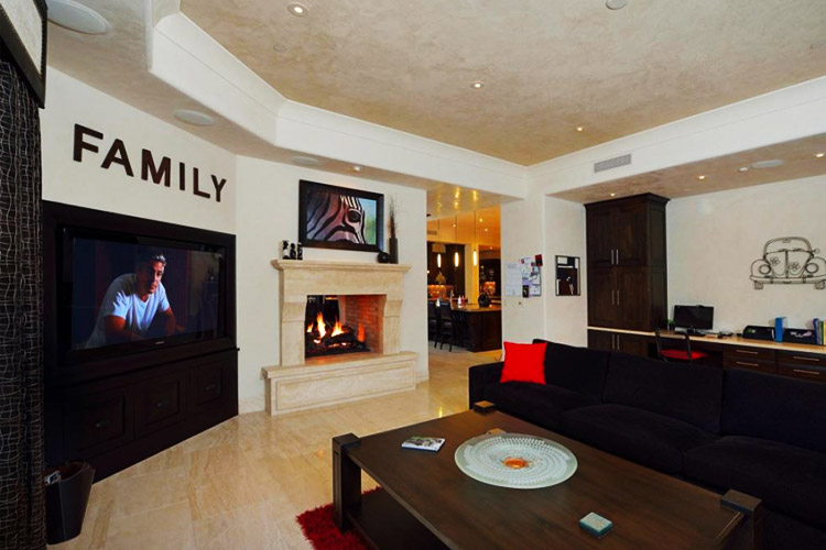 Entertainment room in custom home with TV and fireplace