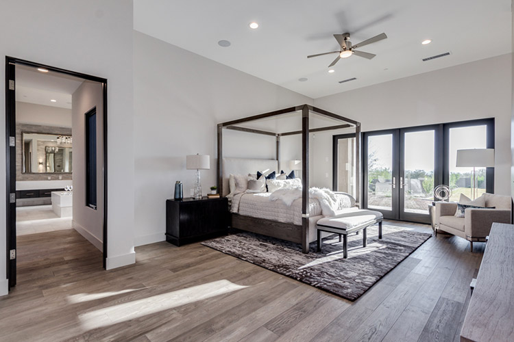 Master bedroom in custom home with canopy bed and fireplace