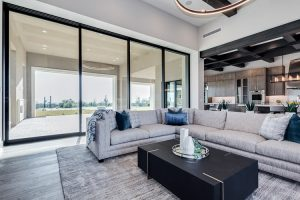 Living room in custom home with view of patio and kitchen