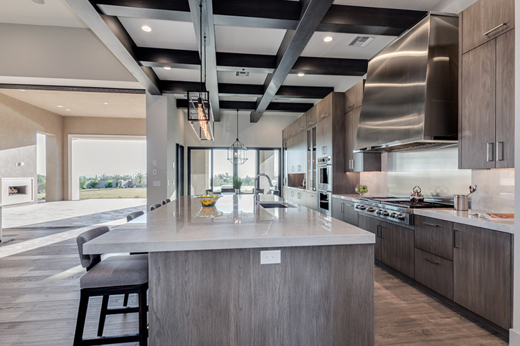 Kitchen in custom home that opens to living room and patio