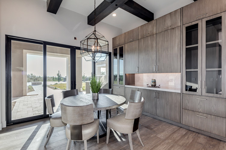Dining area in custom home with view of patio